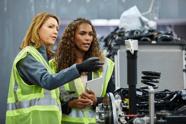 Female engineer pointing to colleague at factory Mature female supervisor pointing to colleague by car part at factory. Confident engineers are discussing over car chassis at automobile industry. They are wearing reflective clothing. mechanical engineering stock pictures, royalty-free photos & images