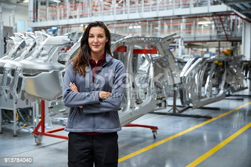 941796726istockphoto Female engineer standing against car chassis 913784040