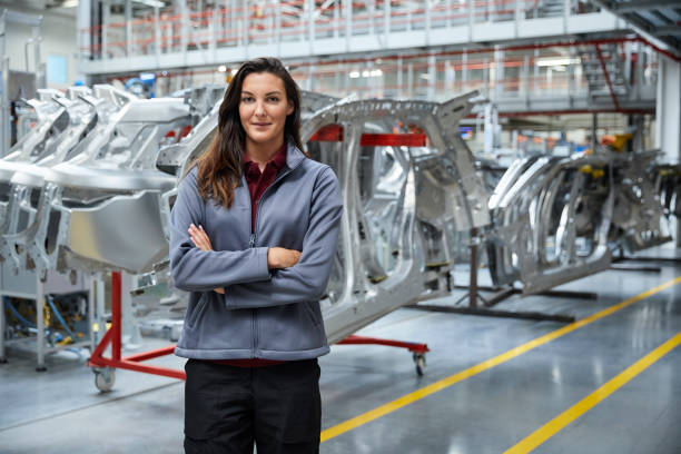 Female engineer standing against car chassis stock photo
