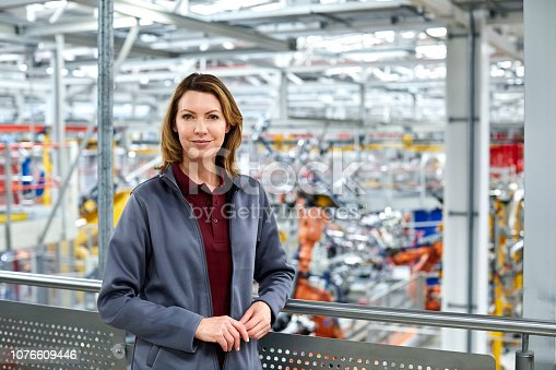 Portrait of female engineer standing in automobile industry. Confident technologist is smiling in factory. She is wearing uniform.