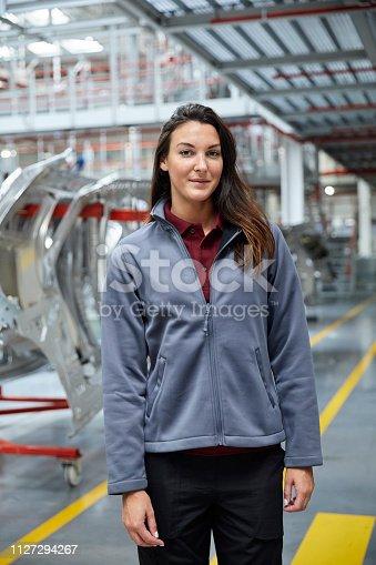 istock Female engineer standing in automobile industry 1127294267
