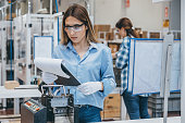 Professional young industrial factory woman employee working with machine parts reading and taking necessary notes with a notepad and a pen while inspecting industrial machine checking, analyzing and testing industrial equipments cables in large electronics factory warehouse