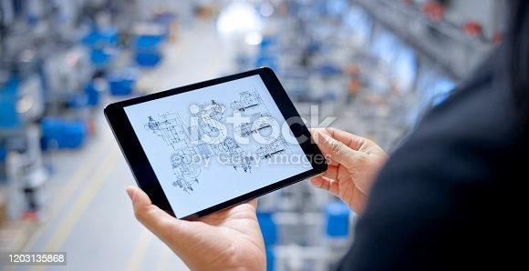 Close-up of female engineer examining engineering drawing on digital tablet.
