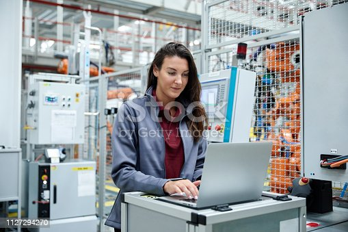 821521124 istock photo Female engineer using laptop car industry 1127294270