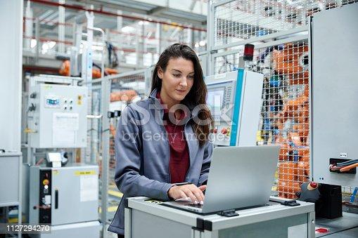 istock Female engineer using laptop car industry 1127294270