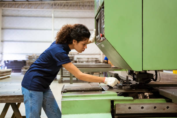 Female engineer using puller machine in factory stock photo