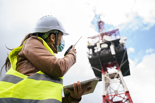Engineer working on the field near a city Telecomunications tower, checking the condition of the Equipement. Technology and Global Business.