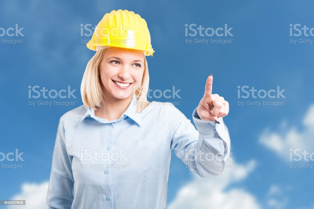 Female engineer wearing helmet using touchscreen stock photo