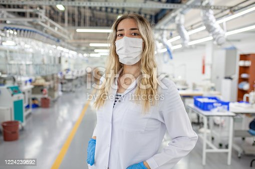 Female engineer wearing protection mask,working at factory during covid-19
