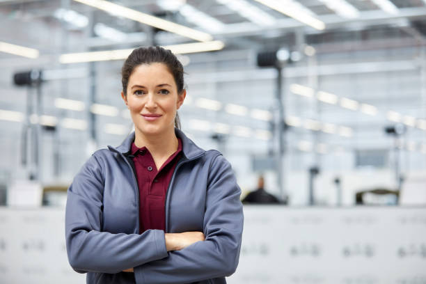 Female engineer with arms crossed in car plant Portrait of female engineer with arms crossed in automobile industry. Confident technologist is standing in showroom. She is in jacket at factory. one mid adult woman only stock pictures, royalty-free photos & images