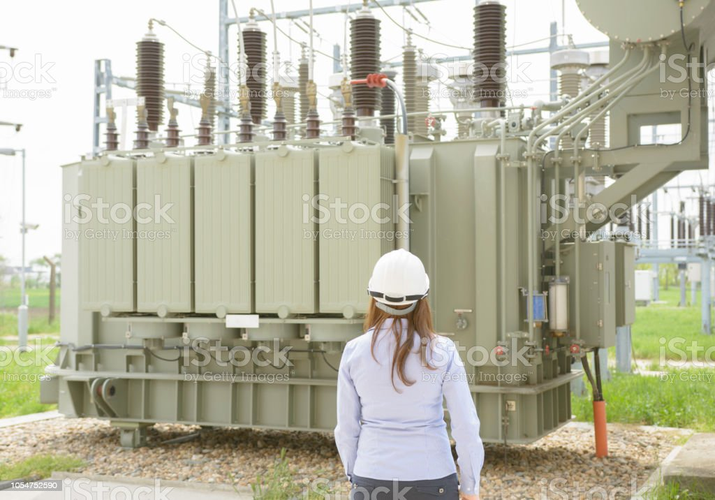 Female Engineer Working Near High Voltage Transformer In