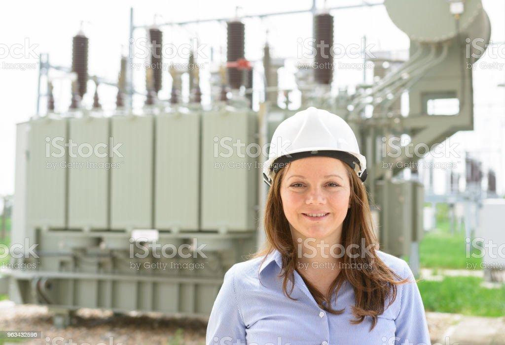Ingénieure en travaillant près de transformateur de haute tension en centrale électrique - Photo de 35-39 ans libre de droits