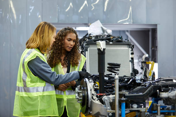 Female engineers discussing over car chassis Female mechanical engineers discussing over car chassis at factory. Confident colleagues are standing by car part at automobile industry. They are wearing reflective clothing. mechanical engineering stock pictures, royalty-free photos & images