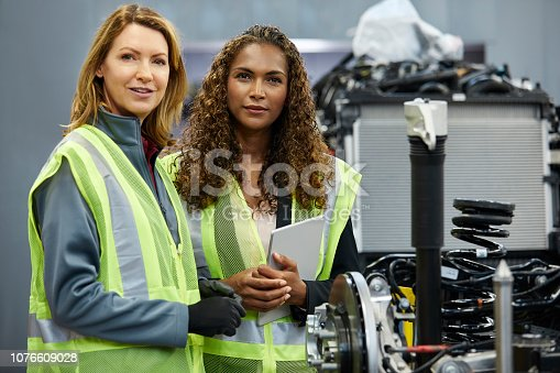 941796726istockphoto Female engineers discussing over car chassis 1076609028