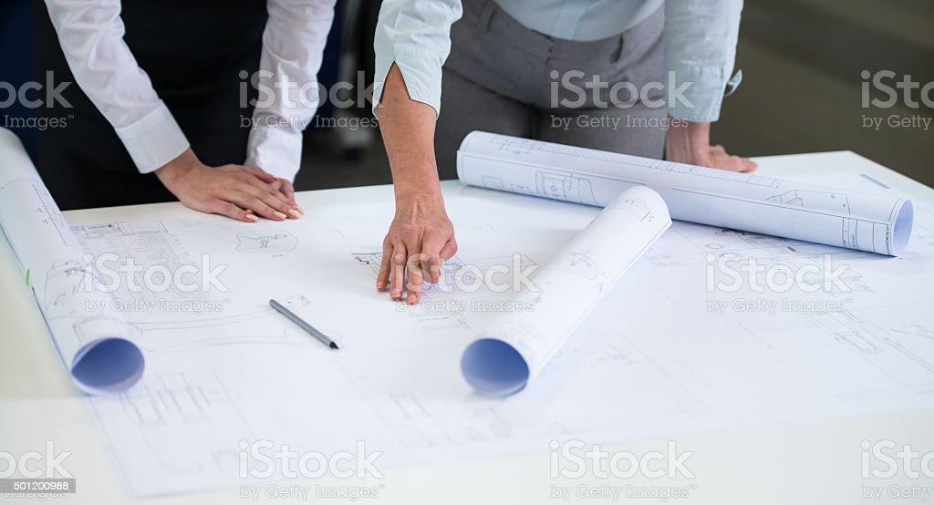 Female Engineers Reviewing Blueprints Together