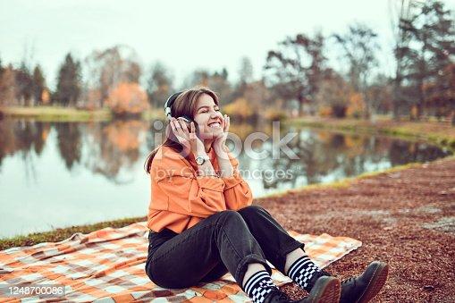 Female Enjoying Favorite Songs In The Park With Headphones
