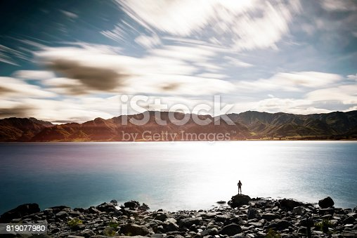 istock Female enjoying the view from the side of the lake 819077980