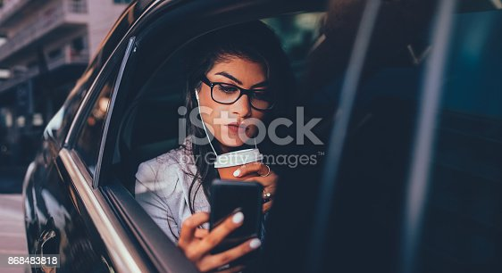istock Female enterpreneur with coffee watching podcast on smartphone in limousine 868483818