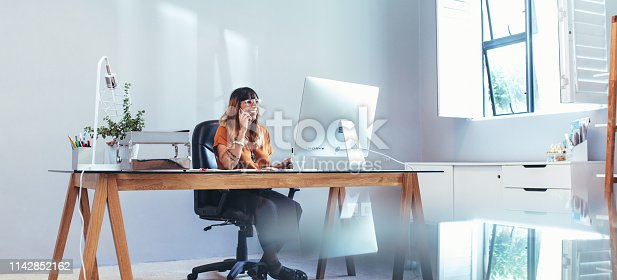 Cheerful woman talking over mobile phone looking at a computer at office. Smiling businesswoman sitting at her table in office working on a computer.
