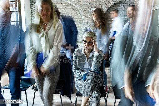 Senior businesswoman having a headache while attending a training class in board room. Her colleagues are in blurred motion.