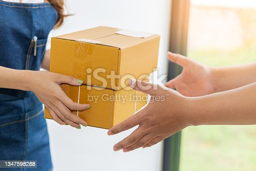 istock Female entrepreneur holding boxes preparing to pack and sell to customers. Online SME business concept. 1347598288