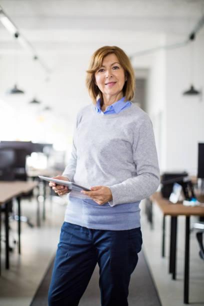 female entrepreneur in office with digital tablet - senior business woman tablet imagens e fotografias de stock