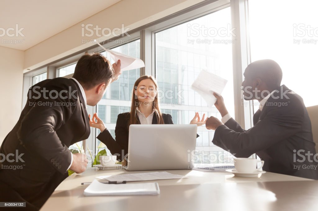Female entrepreneur meditating during hard meeting stock photo