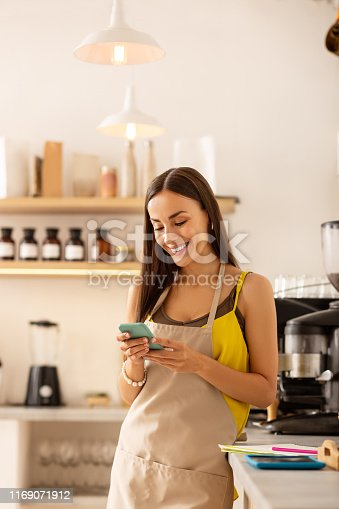 Message on phone. Female dark-haired entrepreneur owning coffee shop reading message on phone