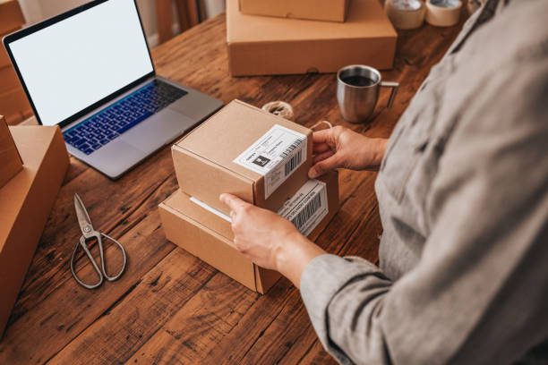 Female entrepreneur preparing the shipment for delivery. Small Business Owner Stock Photo Female entrepreneur preparing the shipment for delivery. sell online stock pictures, royalty-free photos & images