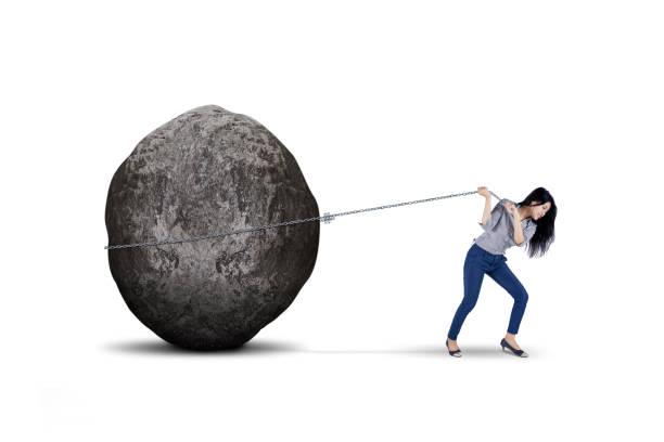female entrepreneur pulling big stone on studio - boulder rock stock pictures, royalty-free photos & images