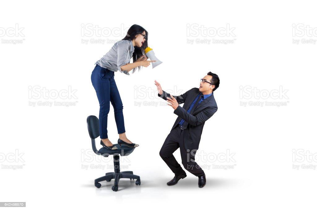 Female entrepreneur shouting with megaphone stock photo
