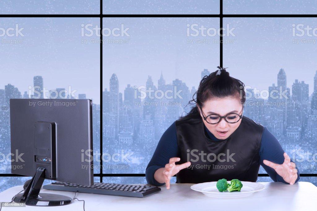 Female entrepreneur wants to eat broccoli stock photo