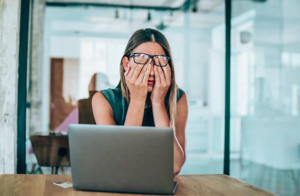 unternehmerin mit kopfschmerzen am schreibtisch sitzen - frustration stock-fotos und bilder