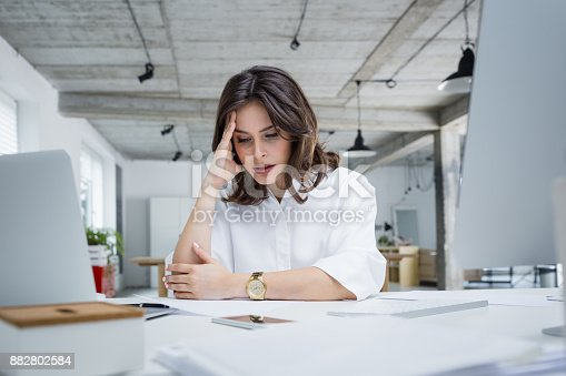Female entrepreneur with headache sitting at desk. Businesswoman under terrible physical tension at work.