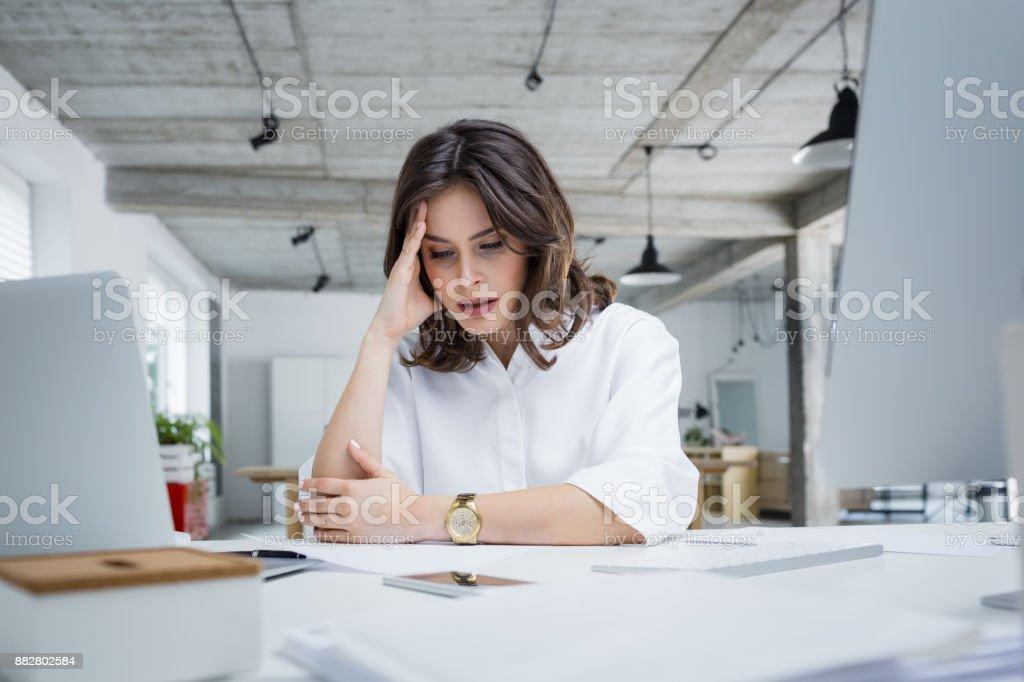 Unternehmerin mit Kopfschmerzen am Schreibtisch – Foto