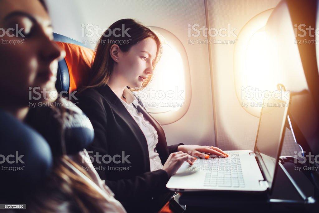 Unternehmerin, die Arbeiten am Laptop sitzt in der Nähe von Fenster in einem Flugzeug – Foto