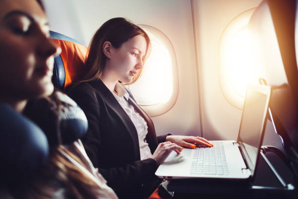 female entrepreneur working on laptop sitting near window in an airplane - wyjazd służbowy zdjęcia i obrazy z banku zdjęć
