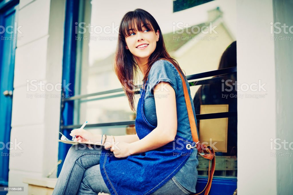Female entrepreneur writing on clipboard while looking away outside deli stock photo