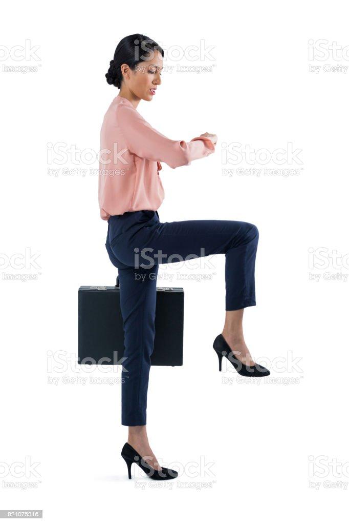 Female executive checking time on white background stock photo