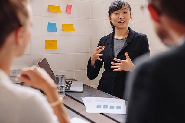female executive explaining new business idea to colleagues. - jacob ammentorp lund stock pictures, royalty-free photos & images