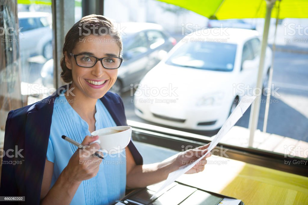 Female executive looking at document while having coffee stock photo