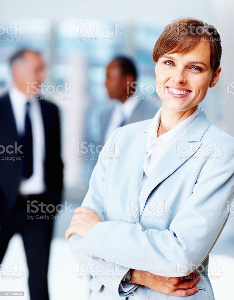 Female executive standing casually with colleagues in background royalty-free stock photo
