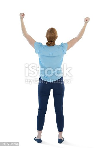 istock Female executive standing with arms up against white background 867708764