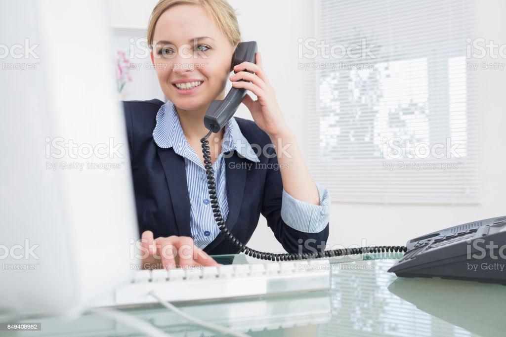 Exécutif femelle à l'aide de téléphone et votre ordinateur au bureau - Photo