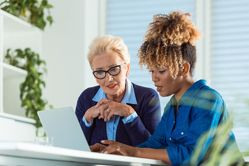 Female Executives Discussing Over Laptop At Desk Stock Photo - Download Image Now