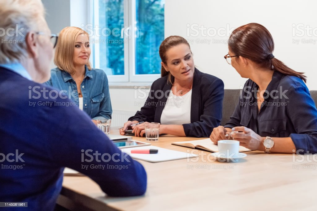 Female executives planning strategy in office Female executives planning strategy in meeting. Colleagues are discussing over new business. They are sitting in board room at office. 35-39 Years Stock Photo