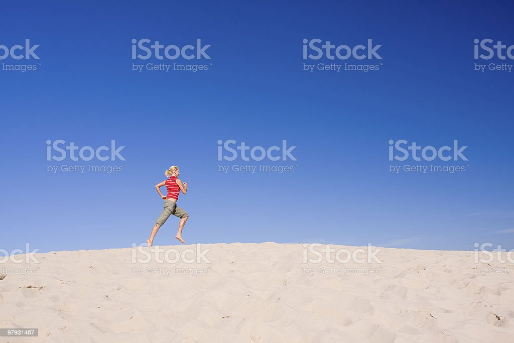 female exercising on a sand dune royalty-free stock photo