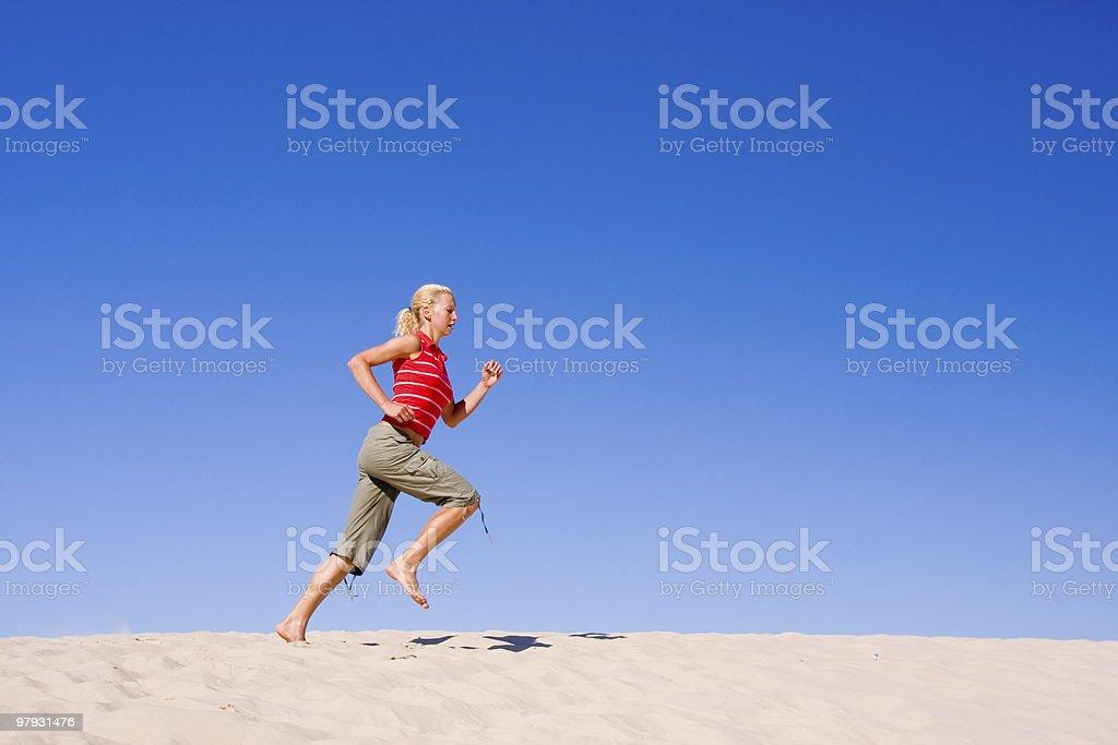 female exercising on a sand dune royalty-free stock photo