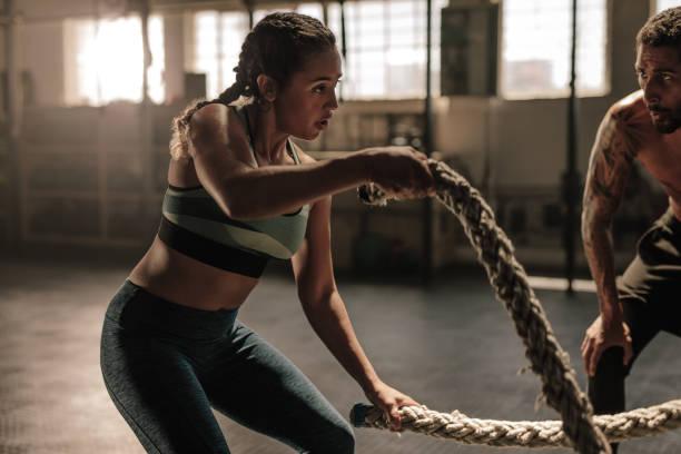 Mujer haciendo ejercicio con cuerdas de batalla - foto de stock