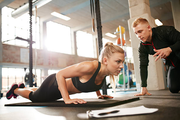 Female exercising with personal trainer at gym stock photo